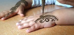 Décoration d'une main d'enfant avec du henné